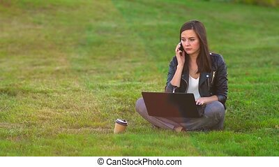 A girl in the Park on the lawn working on a laptop, phone...