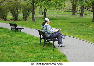 A girl in the park - A girl reading magazine in the park,...