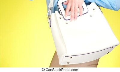 A girl in tight jeans and fashion accessories, a white...