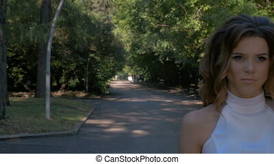 A girl in white clothes walks in the park.