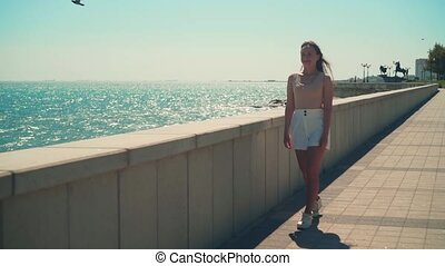A girl in white shorts and a T-shirt with long hair walks along the city promenade.