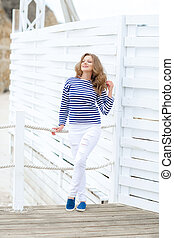 A girl in white tight jeans and sports shoes posing against a white wooden wall. In a sailor t-shirt and glasses. Curly long hair natural color