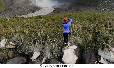 A girl is a professional landscape photographer standing on ...