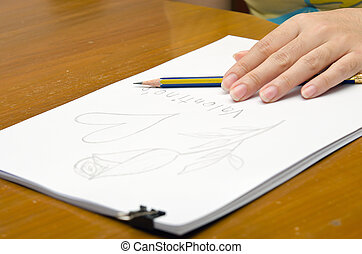 A girl is drawing a rose on a pile of paper