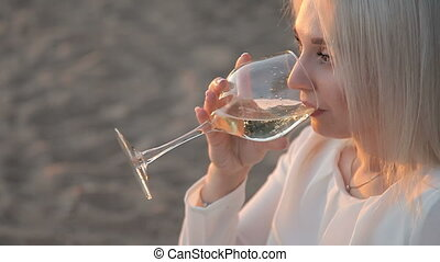 A girl is drinking wine on the beach