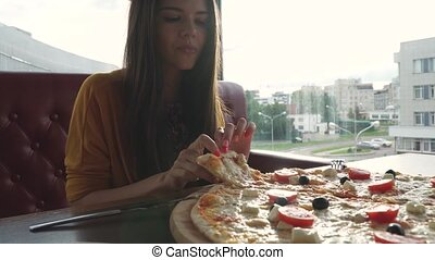 A girl is eating pizza in a cafe. Pizza in cafe. Close up...