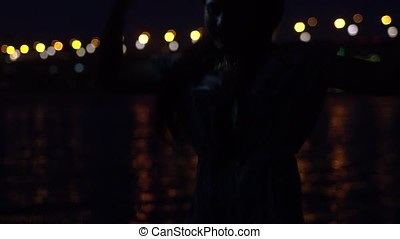 A girl is happy standing on the background of a night city using a smartphone