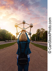 A girl is holding her hands one of the balls at the Atomium monument in Brussels, Belgium.