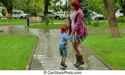 A girl is jumping with a boy in a puddle.