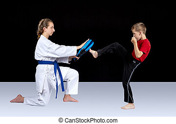 A girl is keeping simulator and boy is training a kick