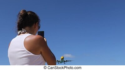 Back side of traveler girl watching the landing plane and taking photo. Woman is photographing a airplane flying in the sky