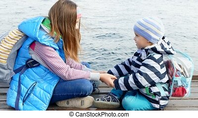 A girl is playing with a baby on the dock. - A girl and a...