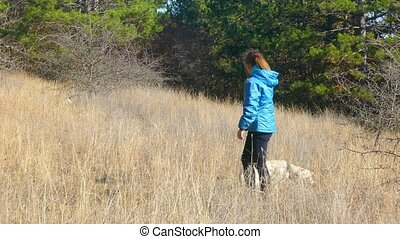 A girl is playing with a dog in the forest. - Girl playing...