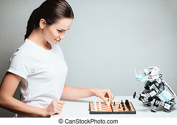 A girl is playing with a robot in chess. The robot sits opposite her on the table.