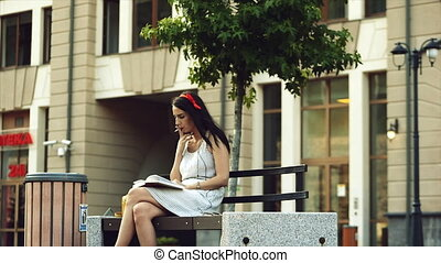 A girl is reading a book in the park while smoking.