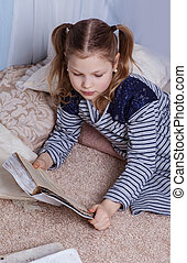 A girl is reading a book lying on the floor