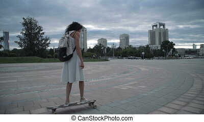 A girl is riding a longboard