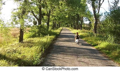 A girl is riding a moped on an alley with trees