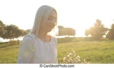 A girl is walking in the park at sunset in the evening