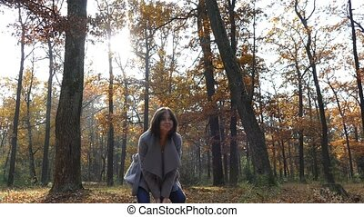 A girl is walking in the park in the fall.