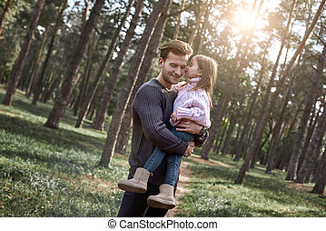 A girl kisses her father in forest