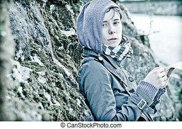a girl lean on the natural stone wall