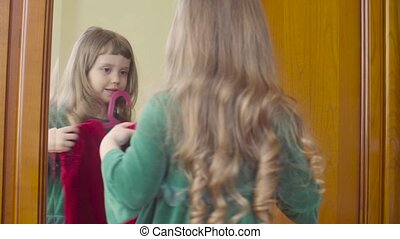 A girl looking in the mirror at a new dress