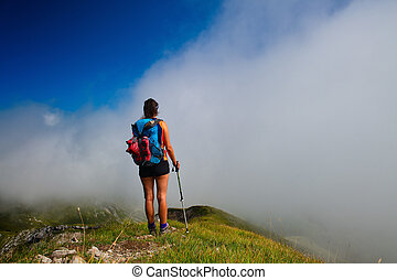 A girl looks afar in the fog at mountain valley during a walk