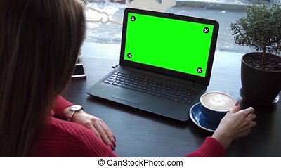 A Girl Looks at a Laptop With a Green Screen
