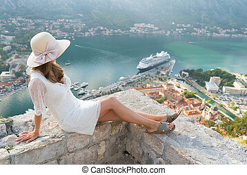 A girl looks from the heights to the Boka Bay of Kotor