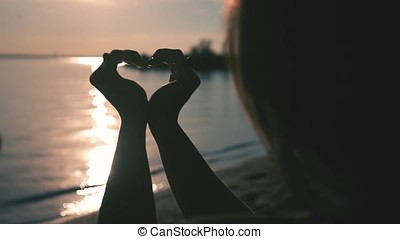 A girl makes a heart symbol with the help of hands during sunset.