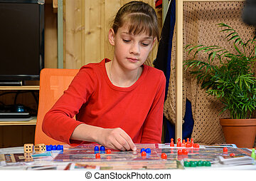 A girl makes another move with chips while playing a board game at the table
