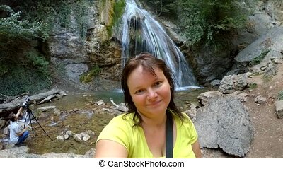 A girl makes selfie on a waterfall background. - The girl...