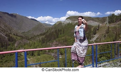 A girl making selfie on a background of mountains and forests