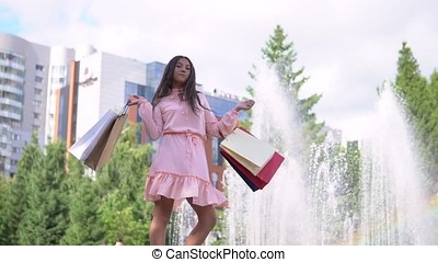 A girl near a fountain in the park after shopping with bags in hand. slow motion.