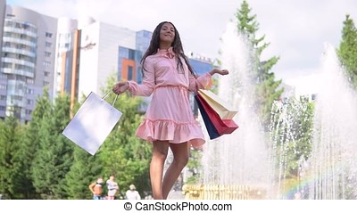 A girl near a fountain in the park after shopping with bags in hand. slow motion. HD.