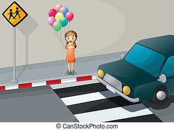 A girl near the pedestrian lane holding balloons