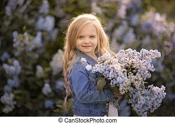 A girl of 5 years stands against the background of lilac bushes and holds a bouquet with flowers in her hands
