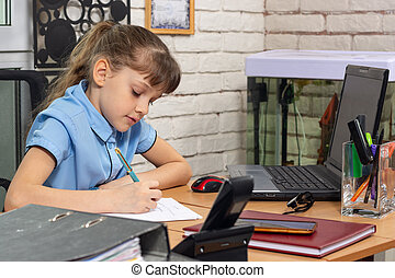 A girl of eight years old works at a table in an office
