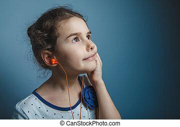 a girl of seven European appearance brunette listening to...