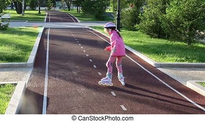 A girl of seven years old learns to skate in the park on a bicycle path