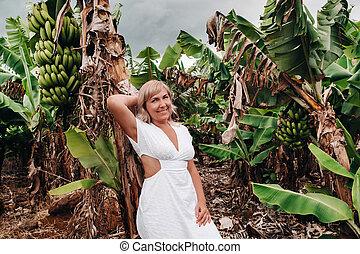 A girl on a banana plantation on the island of Mauritius, a Banana farm on a tropical island, a Girl in a white dress on a plantation in Africa