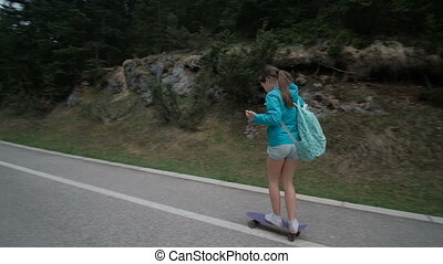 A girl on a skateboard with a backpack rides on the road to the turn.