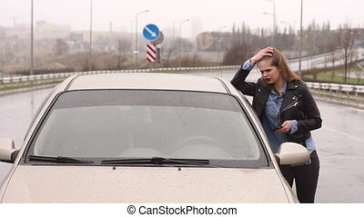 A girl on an empty rainy road asks for help and stops passing cars.