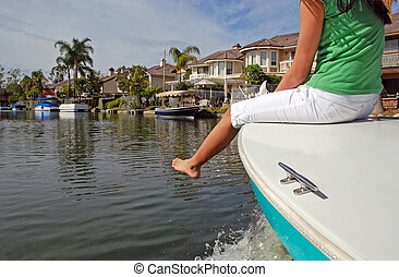 A pretty girl rides on the bow of a boat as it glides over a pretty waterway, passing other boats docked in front of beautiful houses with palm trees in the yards.