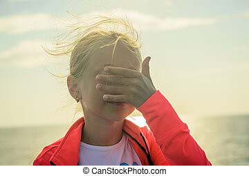 A girl on the beach in the bright sun closes her eyes with her hand.