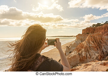 A girl on the coast of the Atlantic Ocean of Portugal, photographs seascapes, the beaches of the Algarve, Falesia. Warm toning.