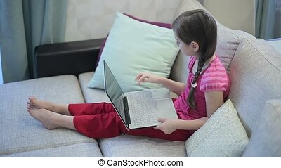 A girl on the sofa is education on a laptop.
