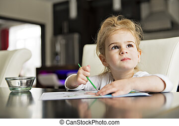 girl painting on the kitchen table at home