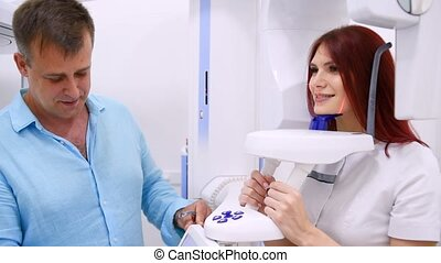 A woman patient makes a panoramic X-ray of the oral cavity using an orthopantomographic apparatus, and an assistant takes a picture